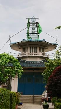 本堂の八角堂の上の塔は塗装の前に必要な接着剤とコーキングで白一色です