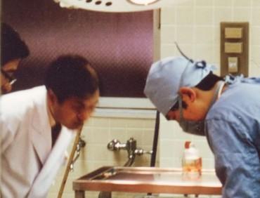 昭和52年1977年 私が病理解剖を始めたころ 以前は外科医でした マスクの執刀医が私 左の臨床医の依頼により解剖を行っています 私は元来が臨床医のためか解剖はつらい仕事でした 写真の左の臨床医の私の手許を視る姿勢から熱心に真実を観察したいという気持ちがわかりますね