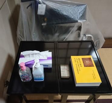 本堂入り口のアルコール 左から消毒用アルコール・ティッシュペーパー、名刺サイズのショップカード(お店ではないのでテンプルカード?)、配布用「福性寺の歴史第7版」、壁ぎわは車椅子です