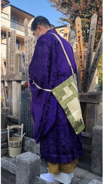 墓前読経 マスクをして読経しています 数珠と引磬(いんきん、柄のついた携帯用の金)を持っています 紫色の衣(直綴)と白衣の間に茶色の裙(くん、腰衣)が見えます 裙は不要とのご意見もあります しかし明治生まれの私の知る範囲の僧侶は裙をつけていました